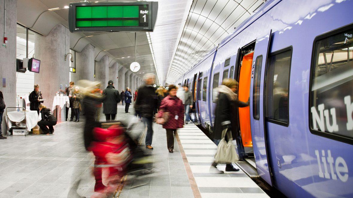 personer går på tåg vid perrong